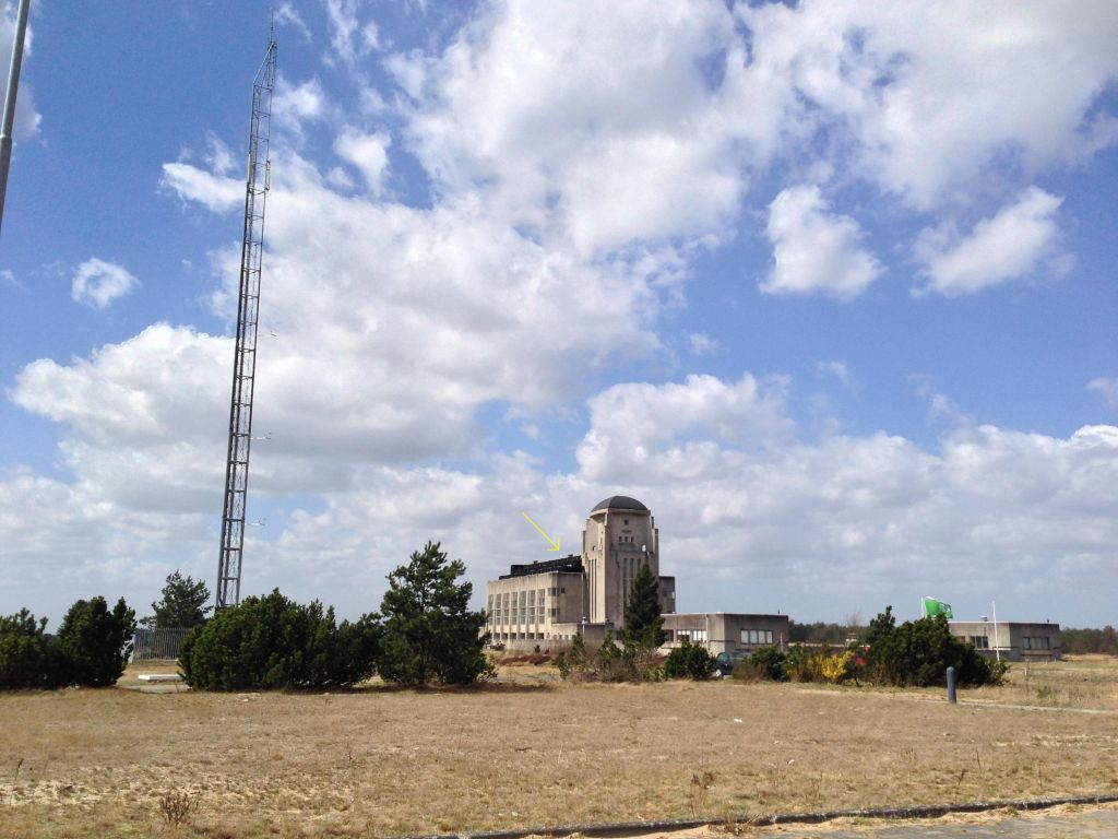 The GNSS antenna is mounted on a short mast on the roof of Radio Kootwijk (nickname Cathedral), nearby, and in sight of, the former Kootwijk Observatory for Satellite Geodesy (KOSG). The building is a very sturdy concrete structure build in the 1930ties to house long wave long distance radio transmitters (now removed). The building is nowadays a protected monument.