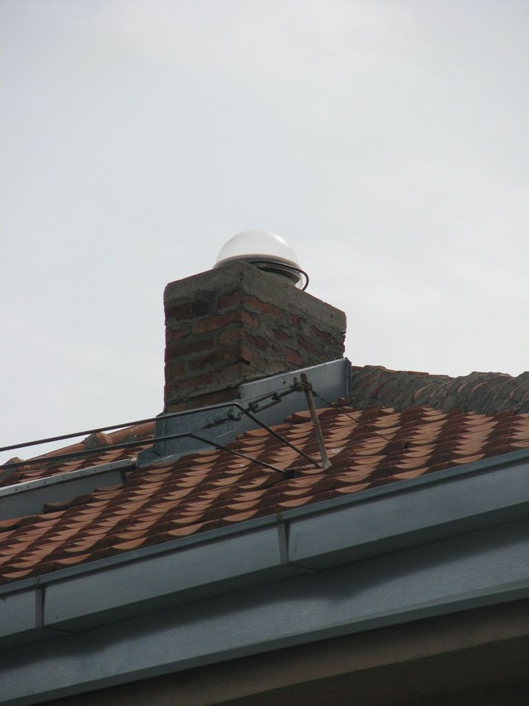 The picture of bricked chimney on the roof of local cadastre building where KNJA CORS antenna is set