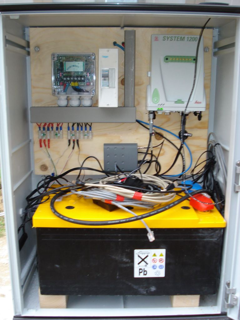 Instrument cabinet with Leica GRX1200GG receiver, solar controller, battery, and GPRS/UMTS modem.