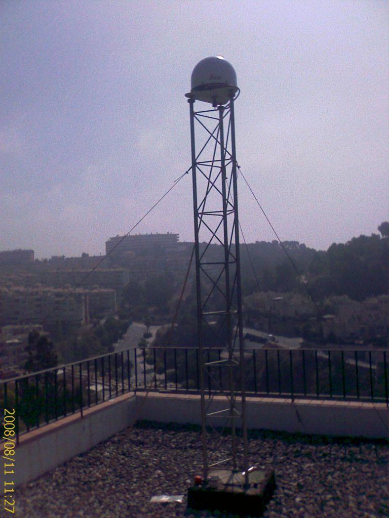 GNSS antenna steel mast on concrete block.