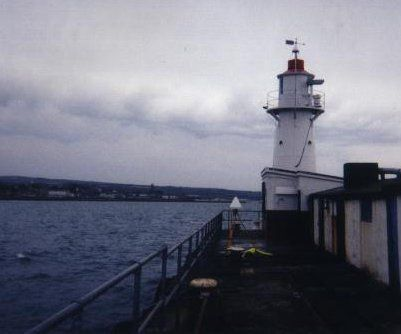CGPS antenna located on the monument mounted on the observation platform of a steel lighthouse adjacent to the tide gauge building (the red and white building at the base of the lighthouse).  A second GPS antenna can be seen, which is located on a bench mark on the pier (which was used as station GB08 in the EUVN97 campaign).