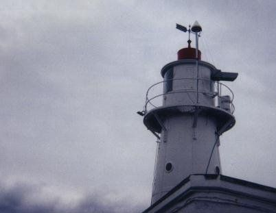 close-up of the CGPS antenna located on the monument mounted on the observation platform of a steel lighthouse adjacent to the tide gauge building (the red and white building at the base of the lighthouse).