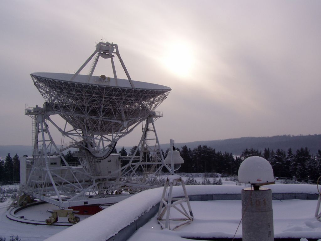 Leica AT504 antenna with radome on the concrete pillar on the roof of 2-store laboratory building at the Svetloe Radio Astronomy Observatory (SvRAO) in about 100 km from St. Petersburg, Russia. The receiver is installed on Dec 1, 2004. On the left - 32-m VLBI radio telescope RTF-32, IVS station SVETLOE, participating in the IVS observing programs till Mar 2003.