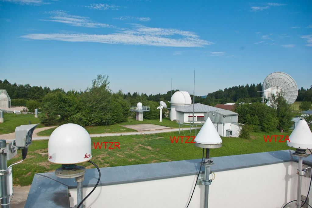 the survey and GNSS antenna tower in the Geodetic Observatory Wettzell with the WTZR, WTZZ and WTZA antenna. In the background the WLRS laser radome and the RTW radio telescope for VLBI.