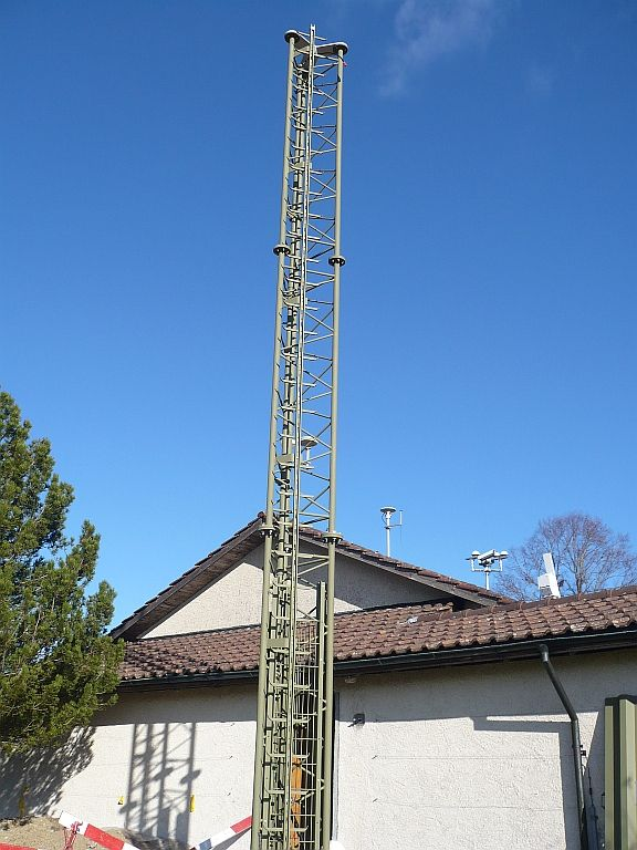 GNSS antenna mounted on a 9-meter steel mast (same construction as ZIMM). View in the direction north-east. The building in the background is the main house of geostation Zimmerwald containing a kitchen and a living room.