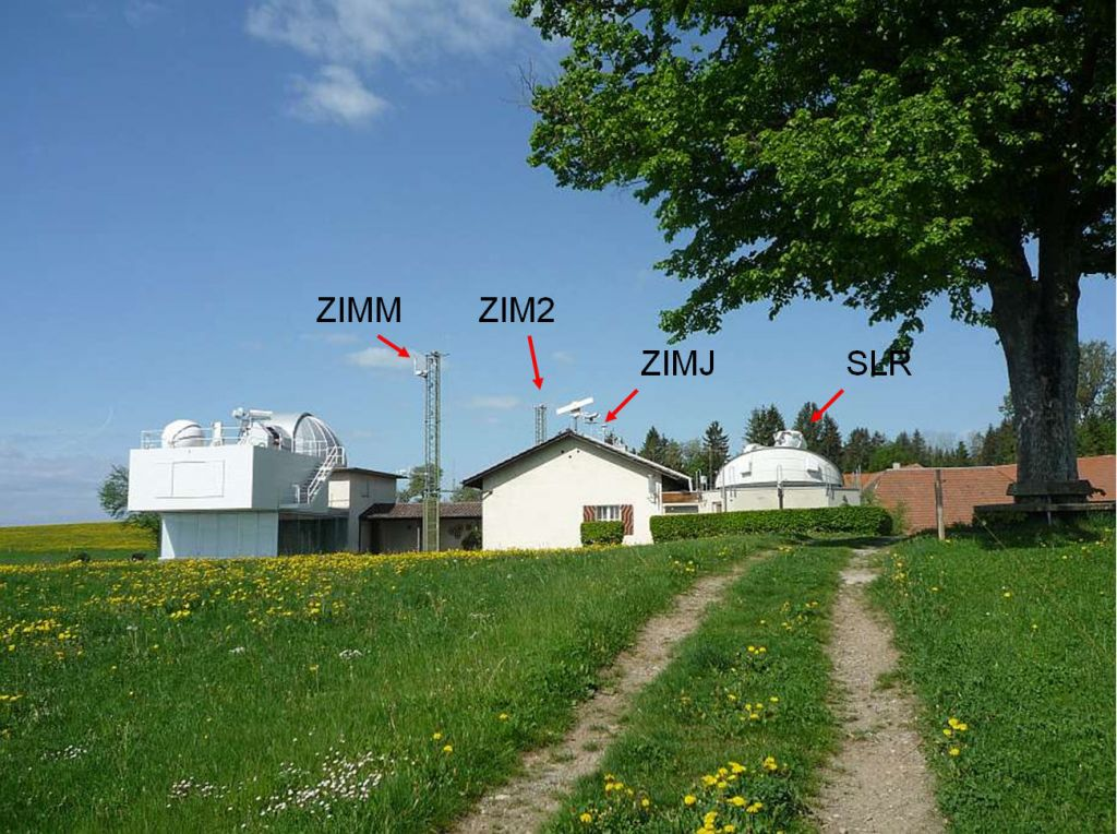 on the left hand side the twin telescope with the 40 cm Schmidt camera and the 60 cm Cassegrain can be seen through the opened dome. The antenna of the permanent GPS receiver (owned and operated by the Federal Office of Topography) is mounted on the 9-meter steel mast. The main house contains a kitchen, a living room, a bed room, a bath, and a computer room. On the roof there are the aircraft detection radar and several additional monuments for GPS and GLONASS antennae. To the right you see the opened SLR dome with ZIMLAT, the ZIMmerwald Laser and Astrometric Telescope.